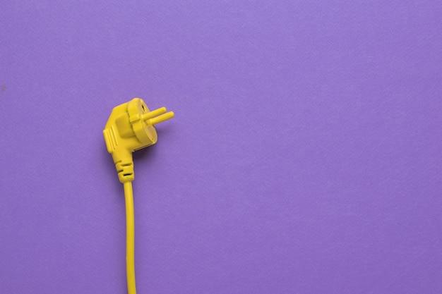 보라색 배경에 노란색 전원 코드입니다. 텍스트를 위한 공간입니다. 세련된 디자인. 전기 제품이 연결된 장소.