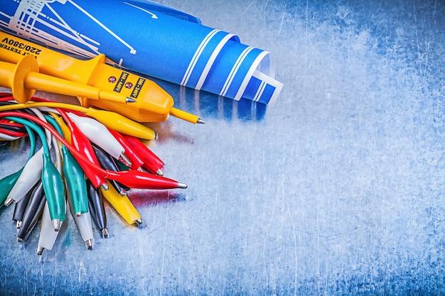 黄色の電気テスタークロコダイルケーブルは、金属の背景の電気の概念に青い建設計画を設定します