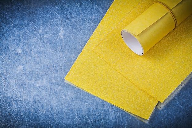 Желтая наждачная бумага на металлическом фоне абразивных инструментов
