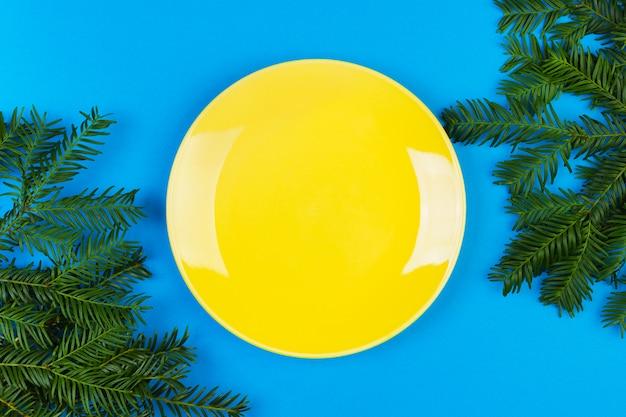 Желтая пустая керамическая тарелка на синей поверхности украшена еловой веткой. вид сверху