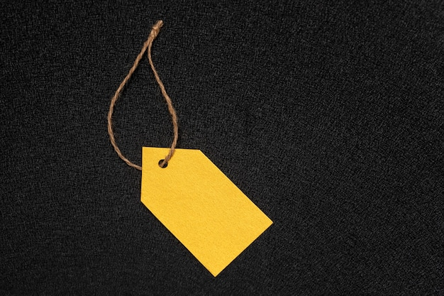 Yellow empty clothing tag on black surface