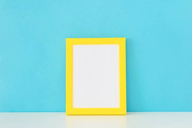 Yellow empty photo frame in front of blue wall