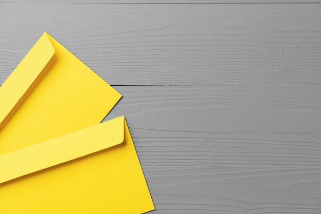 Yellow envelope on gray background top view copy space