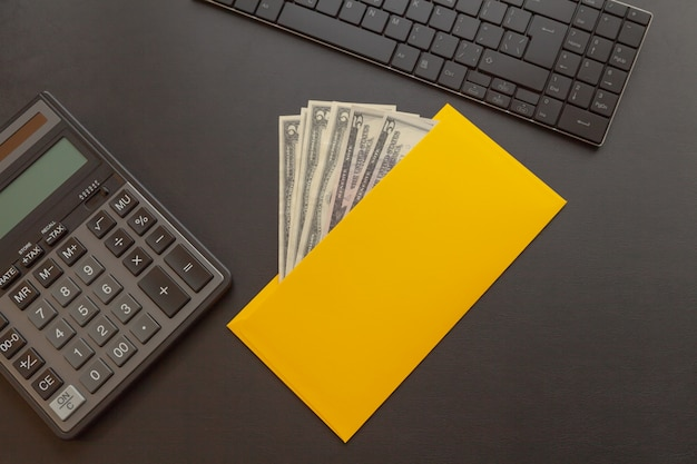 A yellow envelope with money on a dark leather desk, next to a calculator and keyboard.