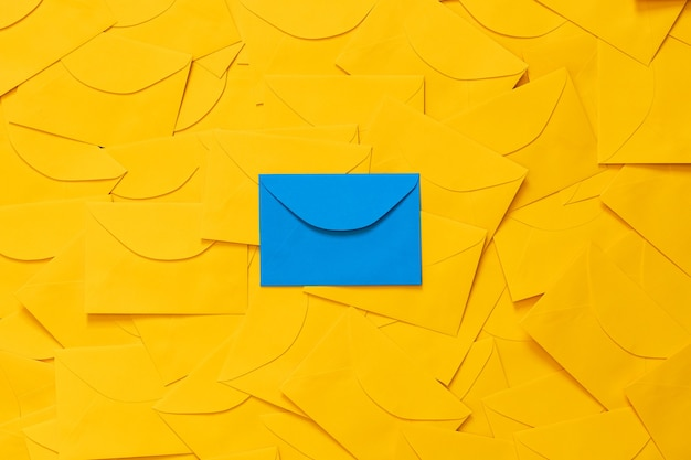 흰 종이에 텍스트를위한 공간이있는 테이블에 흩어져있는 노란색 봉투, 강조 표시된 파란색 봉투, 평면도.