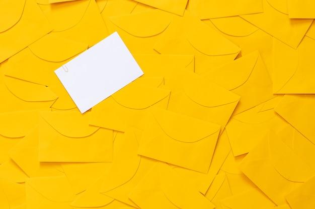 흰 종이에 텍스트를위한 공간이있는 테이블에 흩어져있는 노란색 봉투, 강조 표시, 평면도.