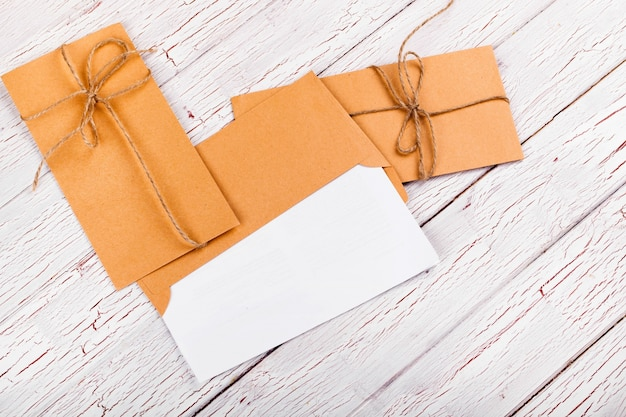 Yellow envelopes twined with rope lie on white wooden table