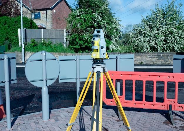 Желтое оборудование установлено на треноге на строительной площадке на фоне безоблачного голубого неба.