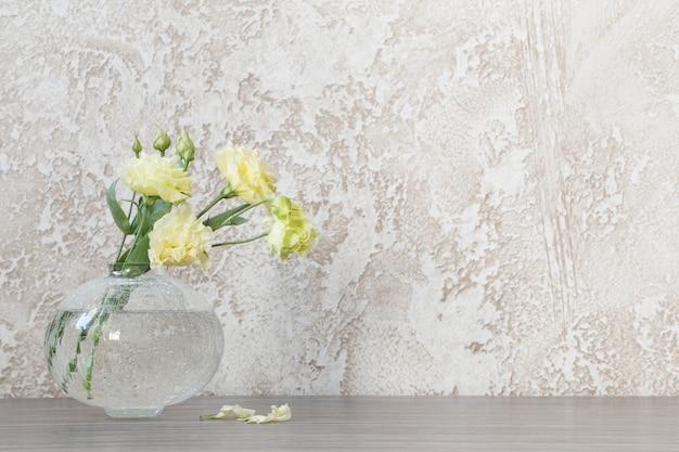 테이블에 유리 꽃병에 노란색 eustoma
