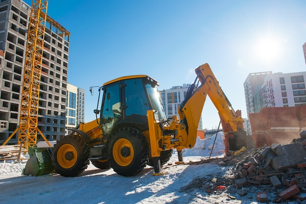 黄色い掘削機は、新しい家を背景に冬に建設現場で地面を掘ります