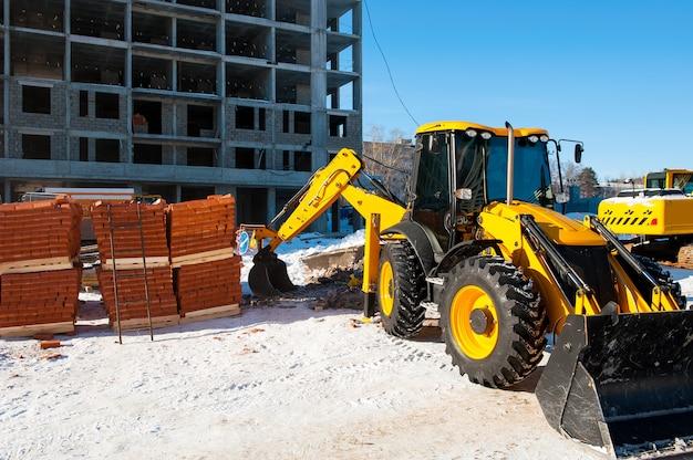 노란색 굴삭기는 새 집의 배경에 대해 겨울에 건설 현장에서 땅을 파다