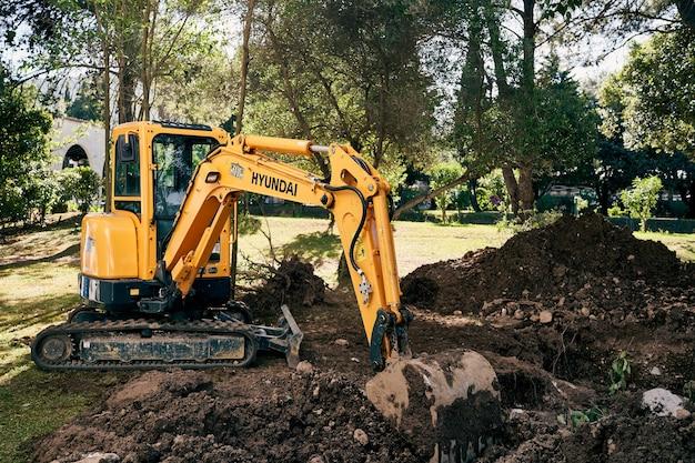 노란색 굴착기는 녹색 공원에서 땅을 파다