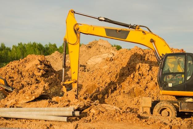 Желтый экскаватор во время земляных работ на строительной площадке. экскаватор копает землю под фундамент и для прокладки канализационных труб централизованного теплоснабжения. землеройная тяжелая техника.