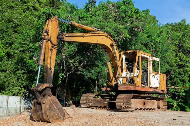 Yellow excavator at the forest and blue sky