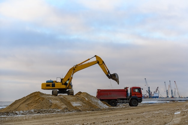 Желтый экскаватор загружает землю в самосвал. строительство дорог.