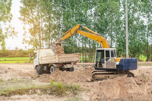 Yellow excavator machine loading soil into a dump truck at construction site