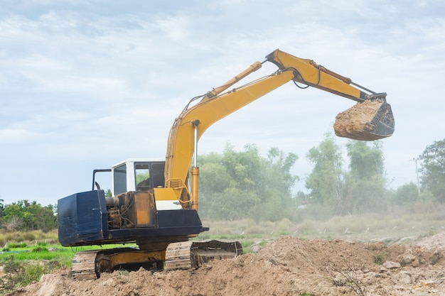Yellow excavator machine working earth moving works at construction site