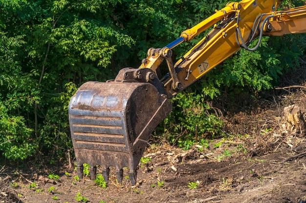 青い空を背景に建設現場の黄色い掘削機。掘削機の腕。閉じる