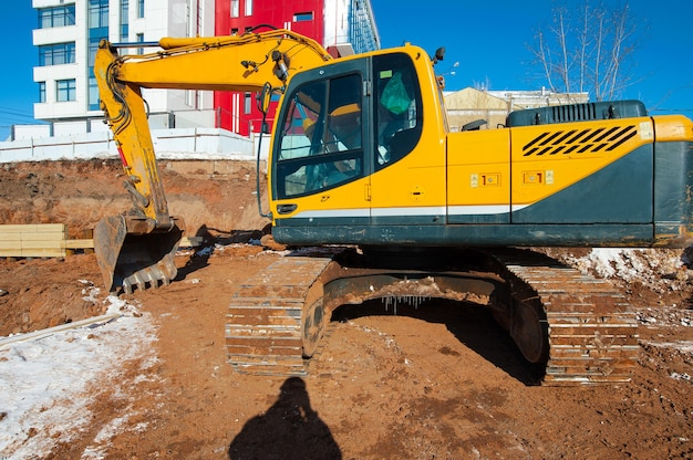 冬の建設現場の黄色い掘削機