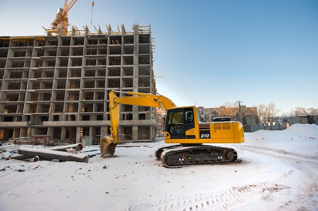 Желтый экскаватор на фоне строящегося зимой нового монолитного дома