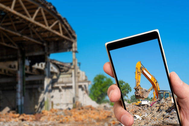 Yellow excavator on screen of smartphone