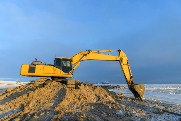 Yellow excavator working on construction site. the road construction.