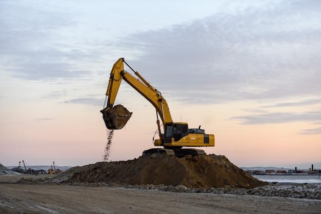 Желтый экскаватор работает на строительной площадке. строительство дорог.