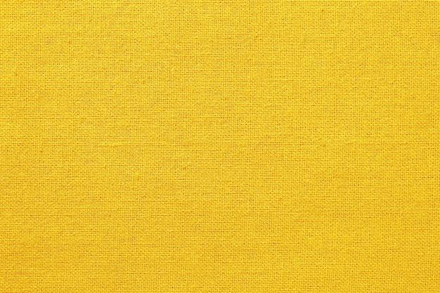 黄色の生地のテクスチャ背景、天然繊維のパターン。