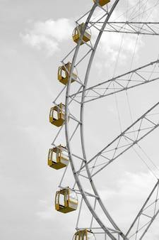 Желтое колесо обозрения против неба.