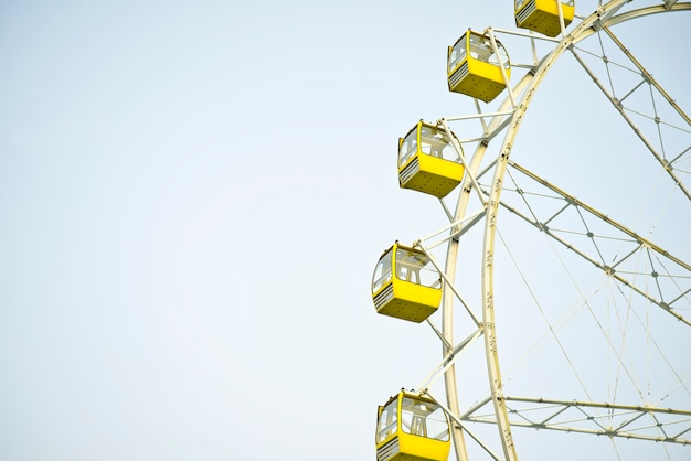 Yellow ferrish wheel with blue sky background