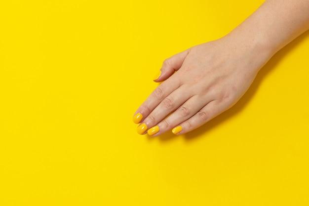 Желтая точка ногтя пальца изолировала желтый фон с лаком для ногтей. покраска ногтей.