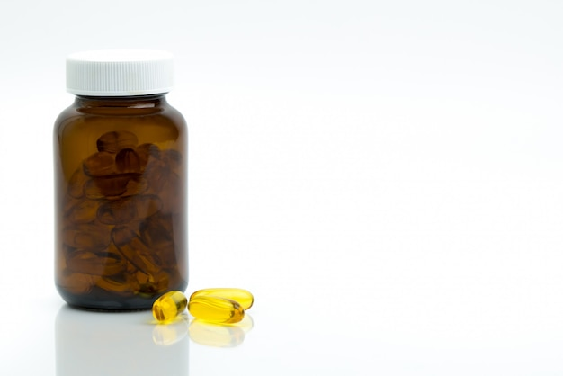 Yellow fish oil capsule pills with amber glass bottle with blank label on the table with copy space for text