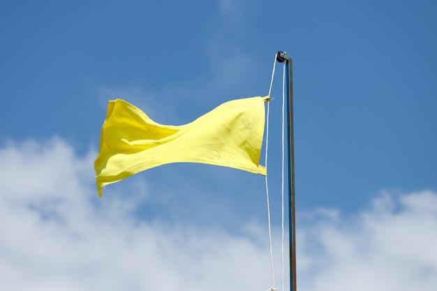 Желтый флаг против неба с облаками. спасательный пост на пляже. фото высокого качества