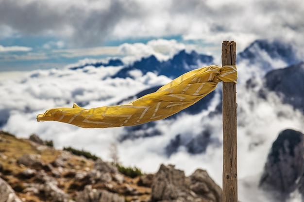 Yellow flag and a view of dolomites covered with clouds in italy