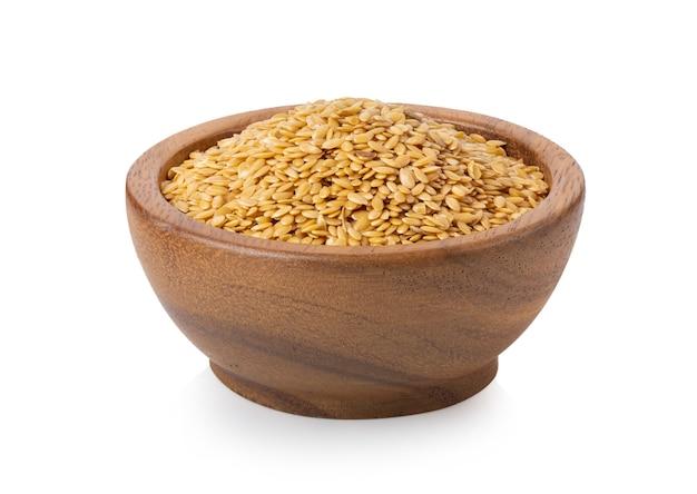 Желтые семена льна в деревянной миске изолированы