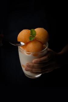 노란 과육 멜론은 아이스크림처럼 둥근 공에 떠서 투명 유리에 담아 신선한 우유를 얹은 달콤하고 맛있습니다. 검정색 배경에 사진 찍기