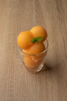노란 과육 멜론 아이스크림처럼 둥근 공에 떠서 투명한 유리 잔에 담았습니다