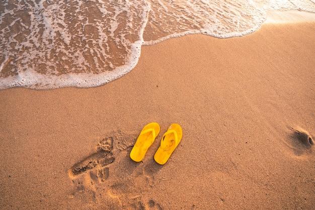 Yellow flip flops on the beach summer evening