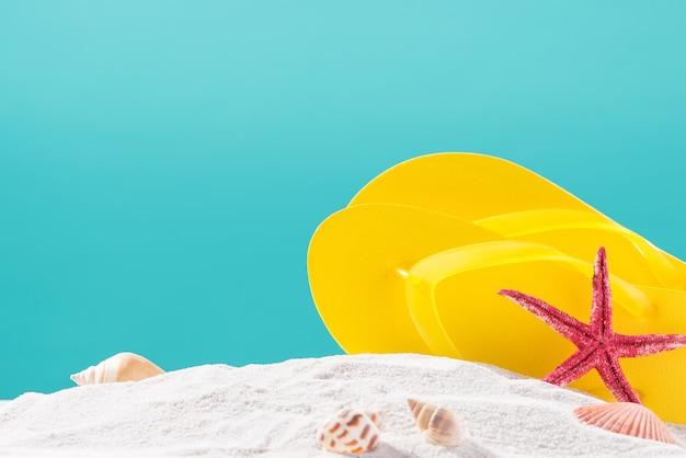 青い背景に対してビーチで黄色のビーチサンダル。