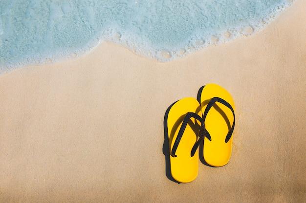 Yellow flip flops on sandy beach.