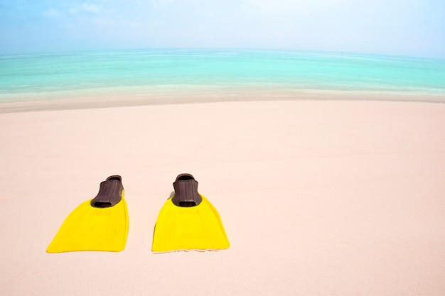 Yellow flippers on the sandy beach