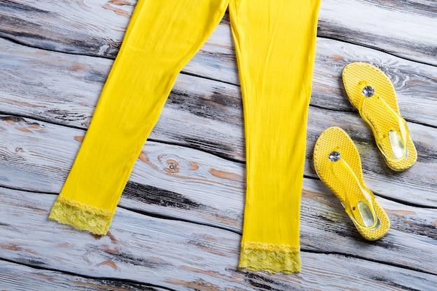 노란색 슬리퍼와 바지. 노란색 바지 옆에 여름 신발입니다. 새로운 항목으로 매장 쇼케이스. 밝고 트렌디합니다.