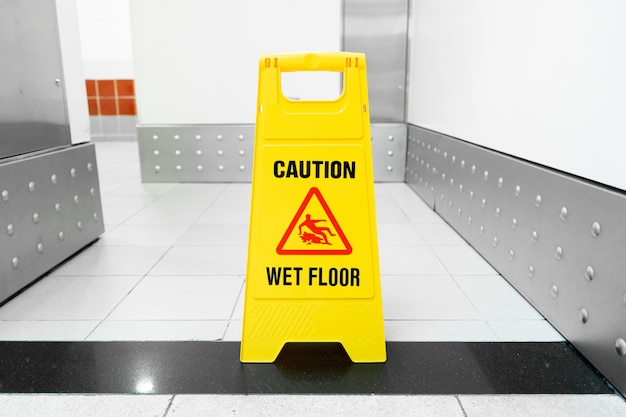 A yellow floor folding sign that draws attention to a freshly washed slippery floor