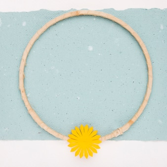 Yellow flower on the empty circular wooden frame over the paper