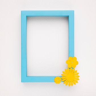 Yellow flower on the wooden blue frame against white background