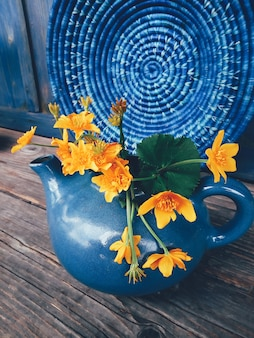 Yellow flowers on blue rustic background