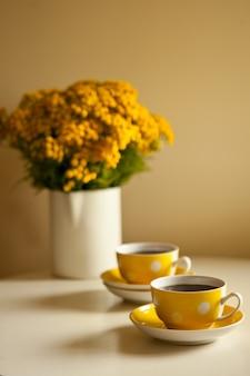 テーブルの上の黄色い花の花束-白い背景の上の2つの黄色いコーヒーカップ、コーヒーブレイクとカフェイン中毒の概念。ヴィンテージデザインとレトロなスタイル