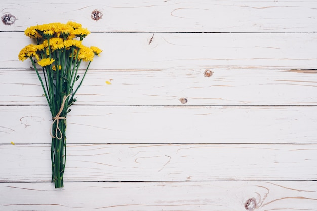 Yellow flowers of bouquet, top view on white wooden background texture with copy space