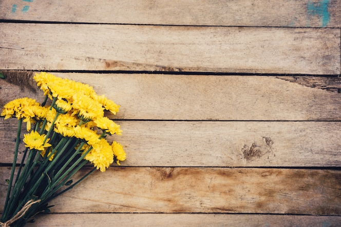 Yellow flowers of bouquet, top view on wooden background texture with copy space