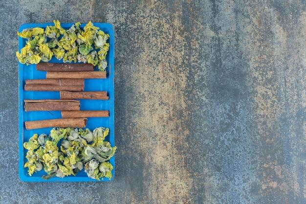 Fiori gialli e bastoncini di cannella sul piatto blu.